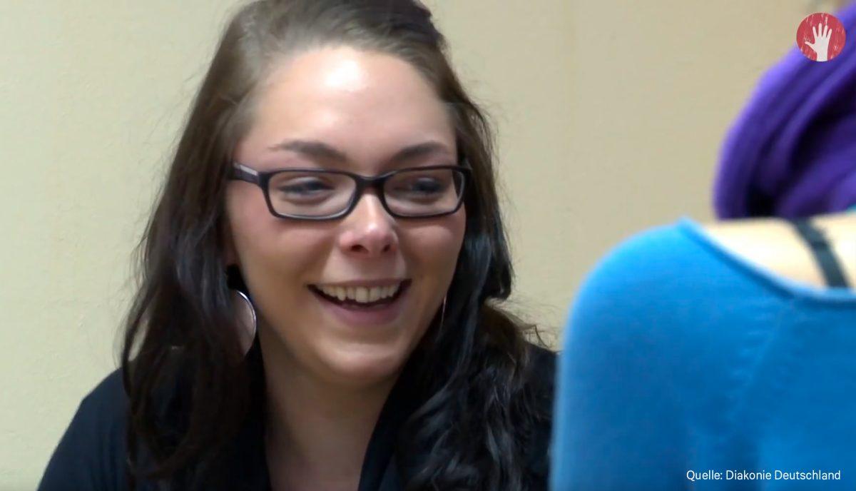 Eine lachende Frau mit Brille und dunklen Haaren